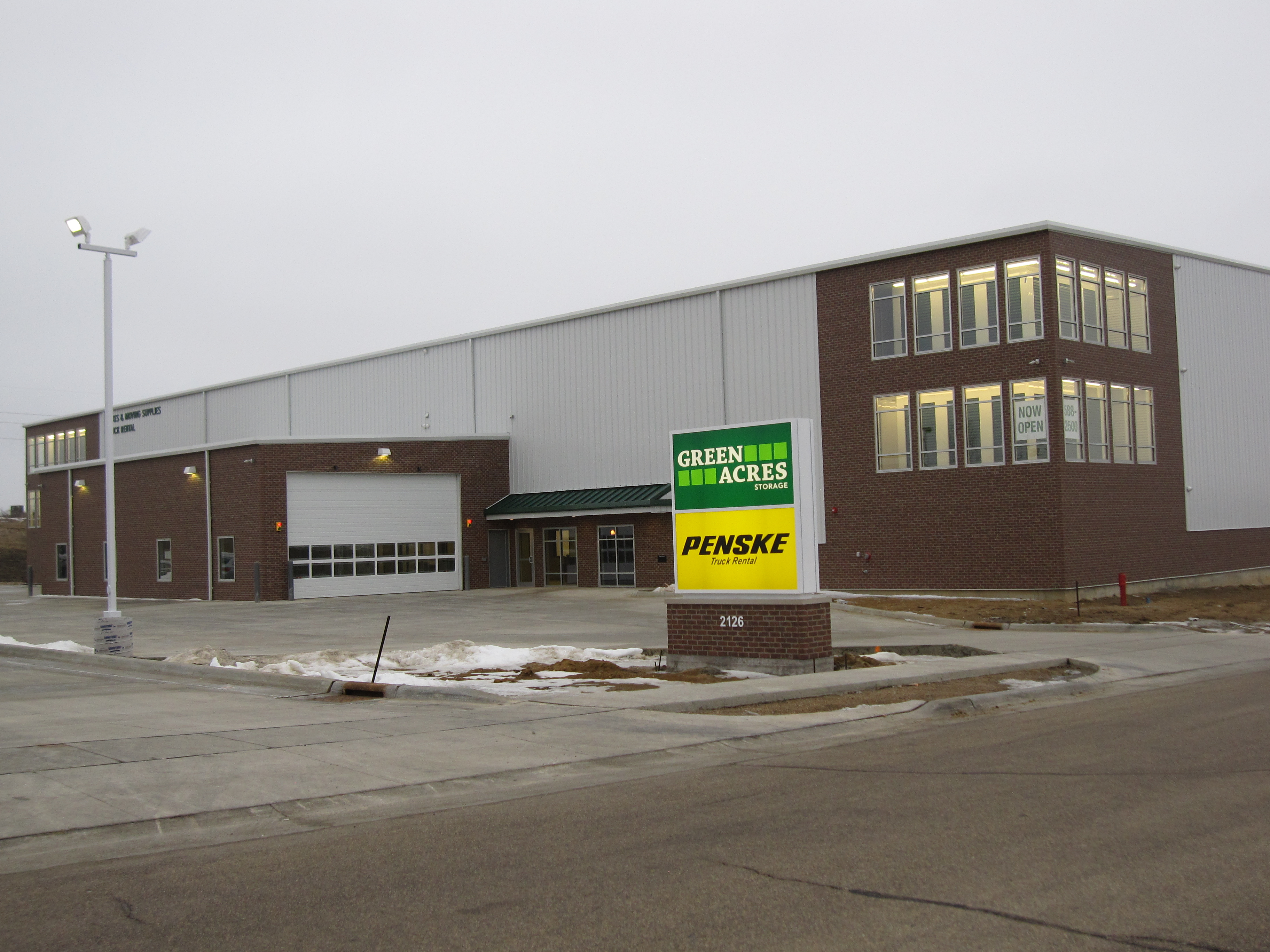 ... As The Many Windows On Each Corner Of The Building Are Lit Up At Night  And Display The Signature Green Overhead Doors Of Green Acres Storage.